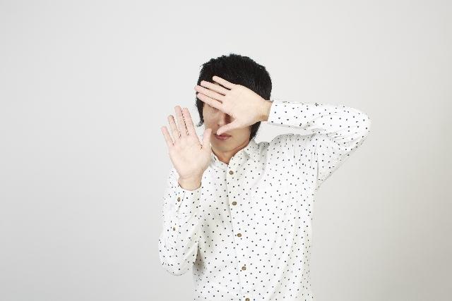 顔を隠す男性